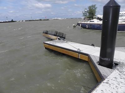 Overturned dock, waves over break wall in background. - PHOTO BY MARINE SURVEYOR GREGORY GROUP