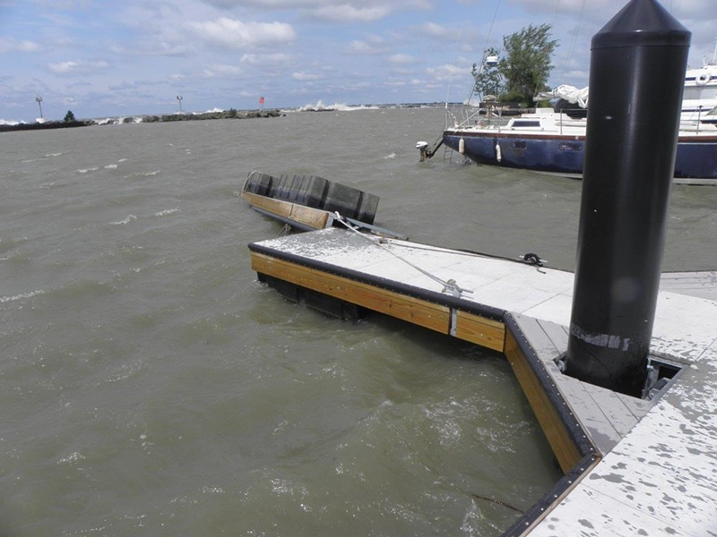 Overturned dock, waves over break wall in background. - PHOTO BY MARINE SURVEYOR GREGORY GROUP