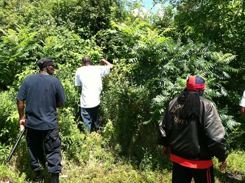 Men scour the woods behind an East Cleveland civic center July 24.
