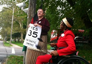 Jason Sonenshein holding sign warning of traffic cameras and urging ban on same. - ERIC SANDY / SCENE