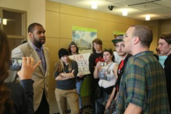 Students speak with administration officials outside President Ron Berkman's office. - EMANUEL WALLACE / SCENE