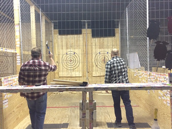 Zachary Clark and Steve Bauer practice before Cleveland Axe Throwing League begins. - PHOTO BY LAURA MORRISON