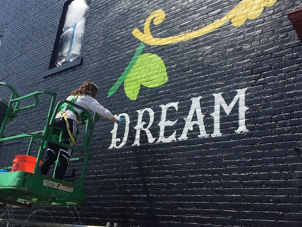 Lisa Quine painting the east wall of 6805 Detroit Avenue - GSAD MURAL PRESS RELEASE