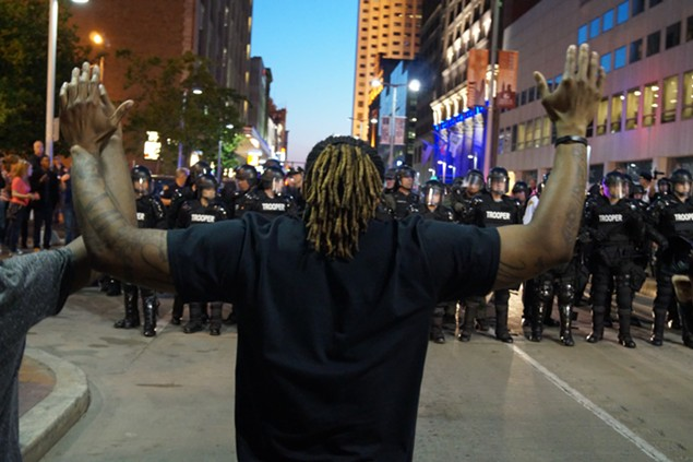 A protester stands before riot police in May, 2015, on the night of the Michael Brelo portests. - SAM ALLARD / SCENE