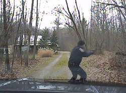 Police officer Ryan Doran draws his gun after exiting his patrol car. Al Merini is never seen in the video.