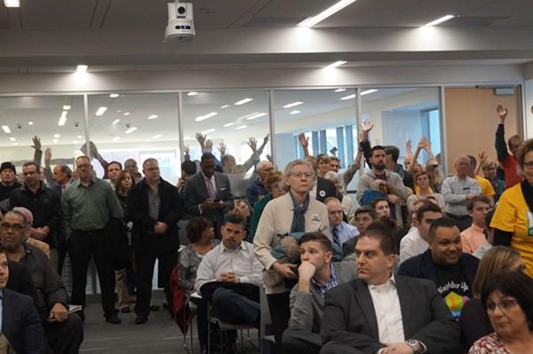 Members of Greater Cleveland Congregations raise their hands. - SAM ALLARD / SCENE
