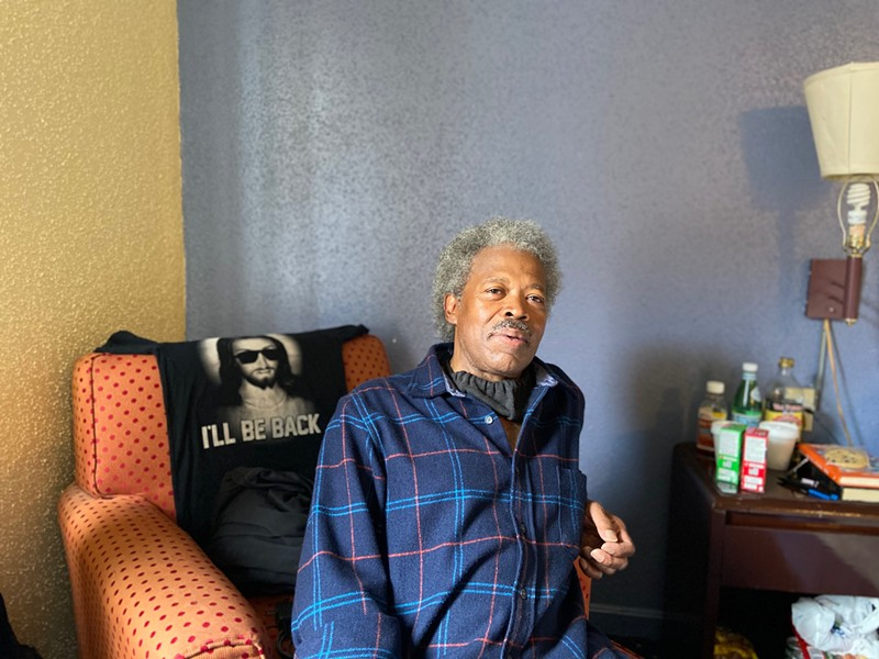 Abel Currie, 63, sits in his hotel room in May. It's been a relief for him to have space to quarantine safely as he searches for a permanent apartment.