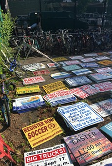 Stolen yard signs from Avon Lake yards found stacked and neatly arranged.
