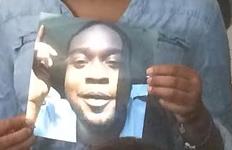 A family member holds a photo of Luke Stewart. - ERIC SANDY / SCENE