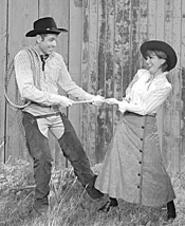 Will Parker (Eric van Baars) ropes in his fickle - sweetheart, Ado Annie (MaryAnn Black).