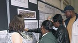 Citizens view large maps detailing prospective plans for DeRenne.