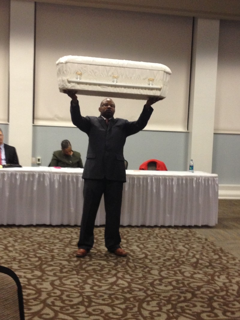 City Council candidate Detric Leggett held up a baby's coffin as a silent protest of the Mayor's record on crime. - JIM MOREKIS