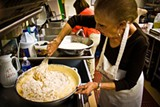 "Clockwise from left: Festival co-founder Peggy Harris whisks flour into what will become dozens of honeycakes, volunteer Joe Polizzi mans the oven and co-founder Ellen Byck divvies up the batter that contains ""liquid gold"" donated by the Savannah Bee Company."