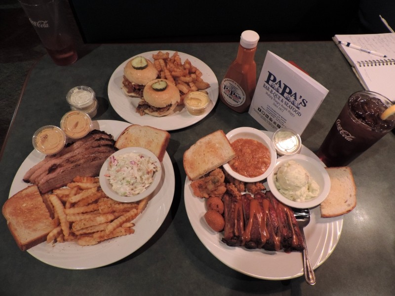 Clockwise from top: BBQ-on-2-buns w/Cajun fries, Ribs & Fried Oysters Combo w/potato salad & Brunswick Stew, Smoked Beef Brisket Platter w/ Cajun fries & slaw