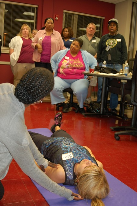 During the first session of the CRI Life Enhancement Program at Curtis V. Cooper Primary Health Care, CRI LEP Core Team member Michelle Grandy (back to camera) discussed proper sleep positions, explaining the importance of adequate rest to being healthy.
