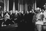 President Lyndon B. Johnson signs the Voting Rights Act of 1965 while Martin Luther King and others look on. Photo by Yoichi R. Okamoto