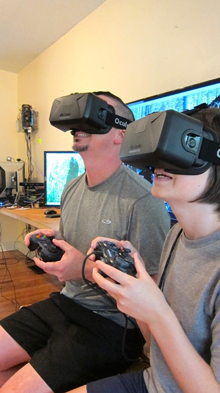 Roberson in his studio with son Clay using Oculus Rift virtual reality technology (custom computer on wall behind)