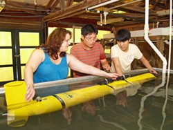 Skidaway Institute scientist Catherine Edwards adjusts a glider's buoyancy with graduate students Sungjin Cho and Dongsik Chan.