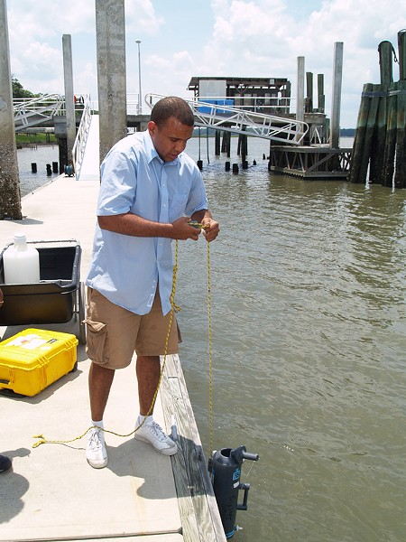 Skidaway Institute's Kevin McKenzie lowers a collection bottle into the Skidaway River to obtain a water sample.