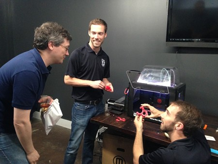Software engineer James Sentman (l.) gets a few pointers on 3D printing from Maven Makers Tim Cone (center) and Ty Donaldson during a lunchtime workshop.