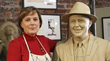 Susie Chisholm poses with the clay model of the statue in her City Market studio.