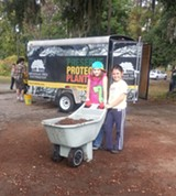 Two small volunteers haul a wheelbarrow full of mulch.