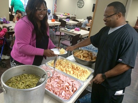 Leggett, right, serves meals at a campaign lunch at the Rose of Sharon Apartments.