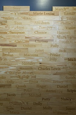 The wall of names of verified enslaved persons who worked in the Owens-Thomas House over the years. - PHOTO BY GEOFF L. JOHNSON