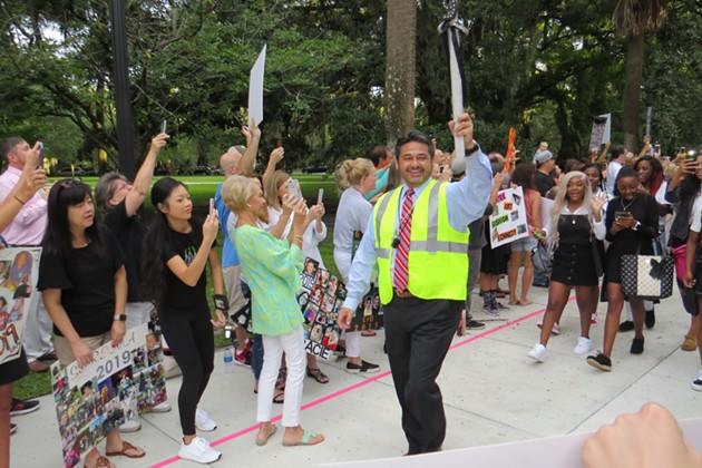 Gif Lockley (voted 2019 Connect Savannah Principal of the year) carrying a glittered scepter and leading the parade of seniors into their first day of school at Savannah Arts Academy (voted 2019 Connect Savannah Public School of the year).