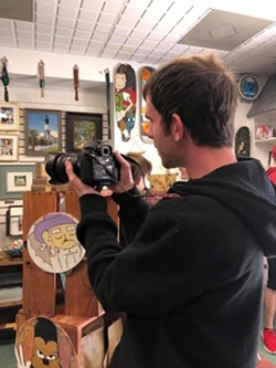 Josh Stewart, a Washed Ashore member, helps out by photographing the items for sale.