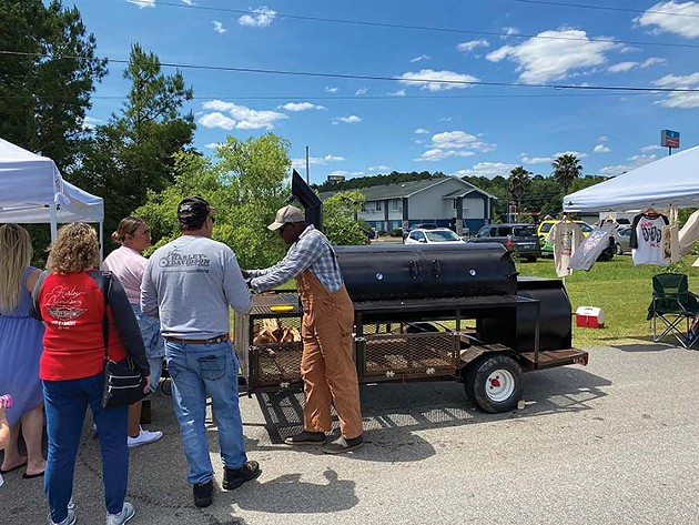Zachariah Parker of Smokin' Jean's Bar-B-Que provides samples to attendees May 15 at the King of the Hog BBQ competition. - PHOTO BY DJ HELLERMAN