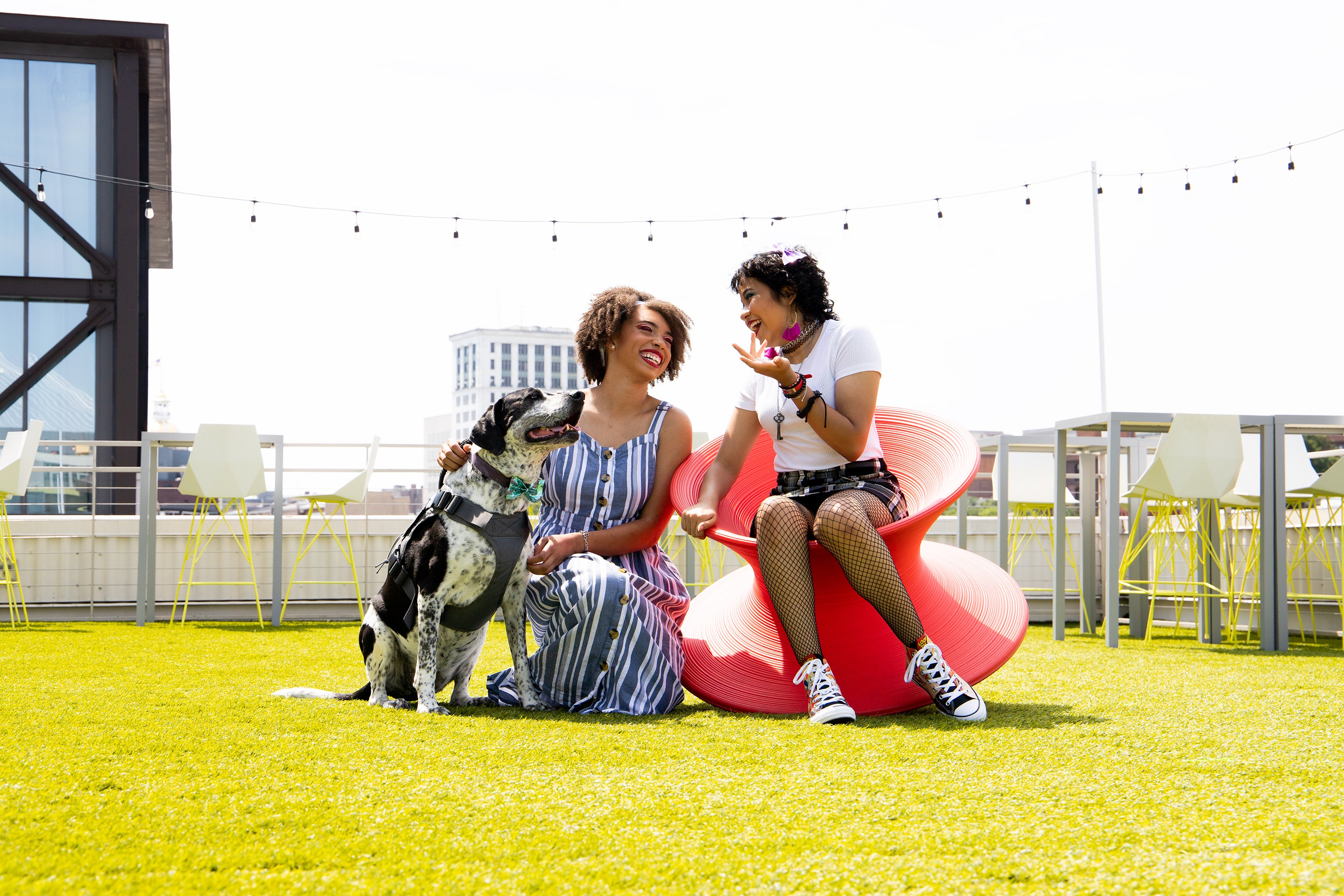 SD Gunner fund beneficiary Sadé Harris laughs with Leilani Tenan and service dog Bambi on the lawn at Electric Moon at Plant Riverside. - PHOTO BY HUNTER MCCUMBER