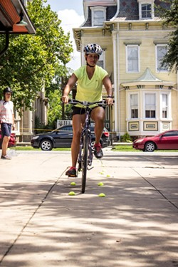 """Caroline Jordan practices a maneuver called the """"Rock Dodge,"""" used to avoid roadway debris that could cause a person on a bike to crash."""