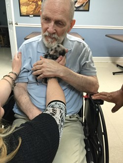 Magnolia Manor resident William Schroder enjoys cuddle therapy with Maggie. - PHOTO BY MYRA BRASWELL