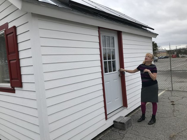 Cindy Kelley shows a model of a tiny home to be constructed for 72 homeless veterans. - Center: