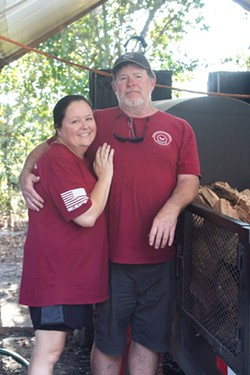 Roy and Mandy in front of their beloved smoker.