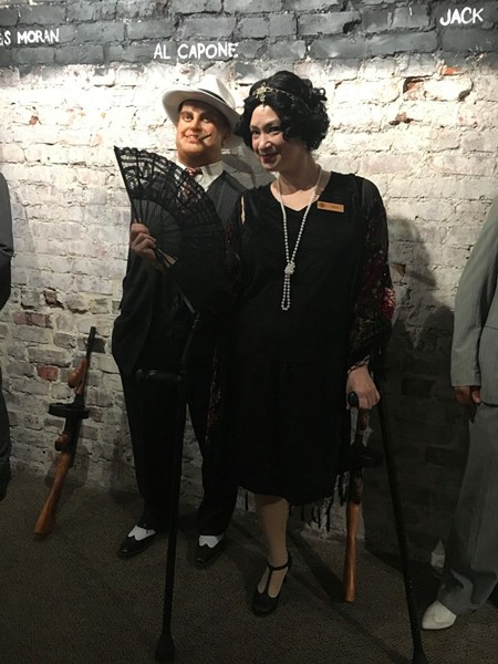 Capone's legend is recounted by beloved theater pro JinHi Soucy Rand, who emulates the Roaring 20s in a drop-waisted dress and feather headpiece.