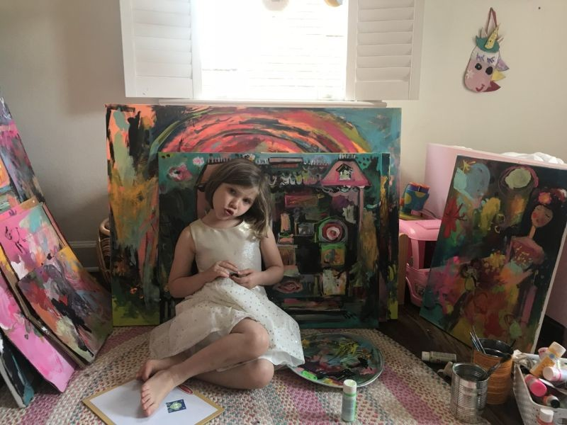 Zelia with her paintings.
