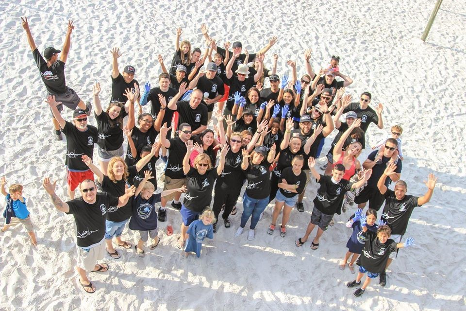 Volunteers celebrate a clean beach as they raise their hands to the pier at Tybee Island beach at a previous year's cleanup.
