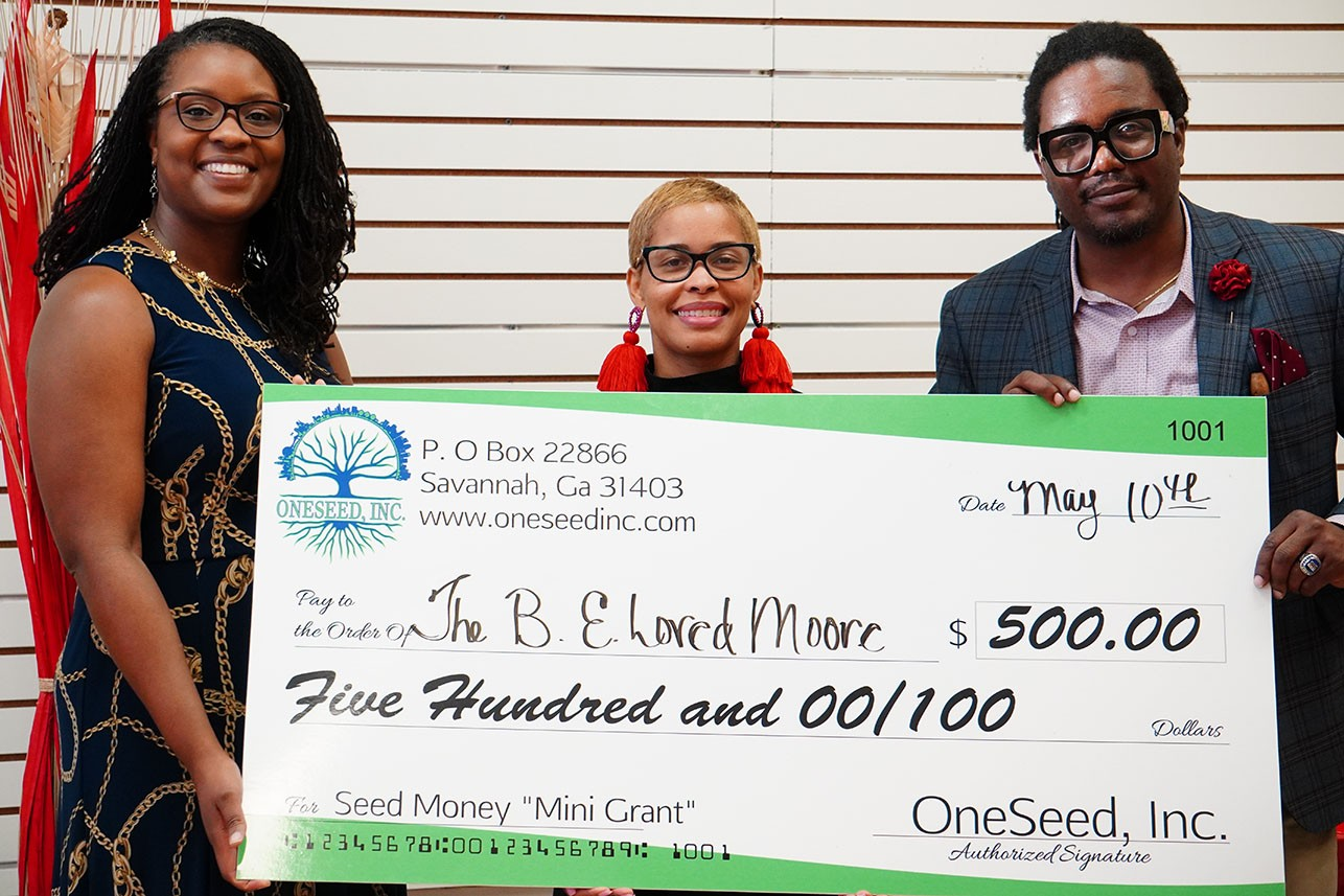 Board members present Latecka Moore-Early of The B.E. Loved Moore Foundation with June minigrant.