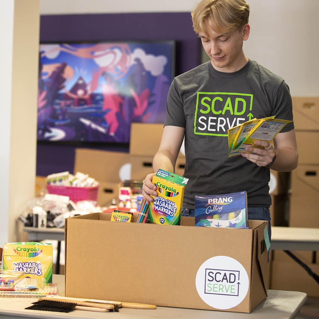Josh Nilsson, a rising junior majoring in Industrial Design, packs boxes of art supplies for a local school.