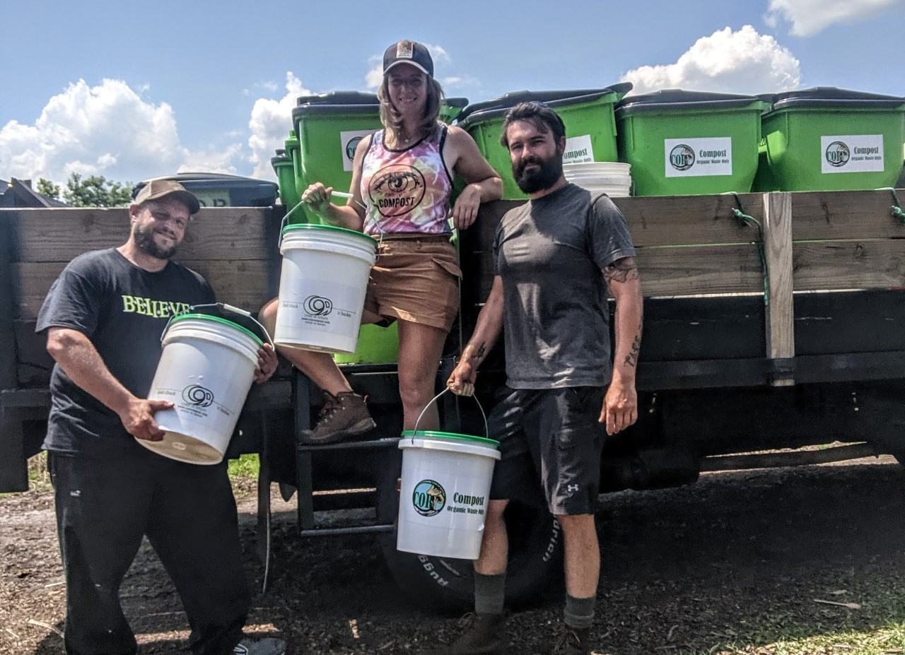 A volunteer displays the Code of Return Compost collection buckets alongside Maria Vaughn and Michael Wedum.
