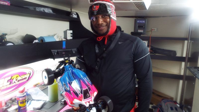 Jermaine Hayes shows off his remote-controlled car and stays warm inside his race trailer.