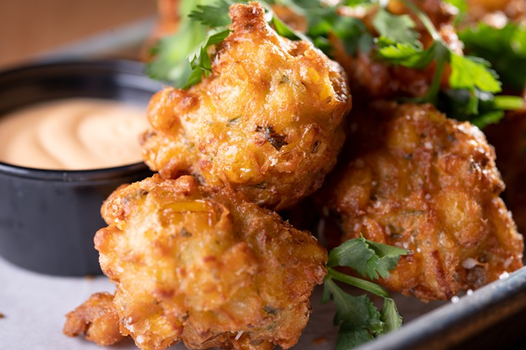 Crunchy corn fritters have sweet whole kernels of corn and are served with a spicy a Sriracha aioli. - ALISON MCLEAN