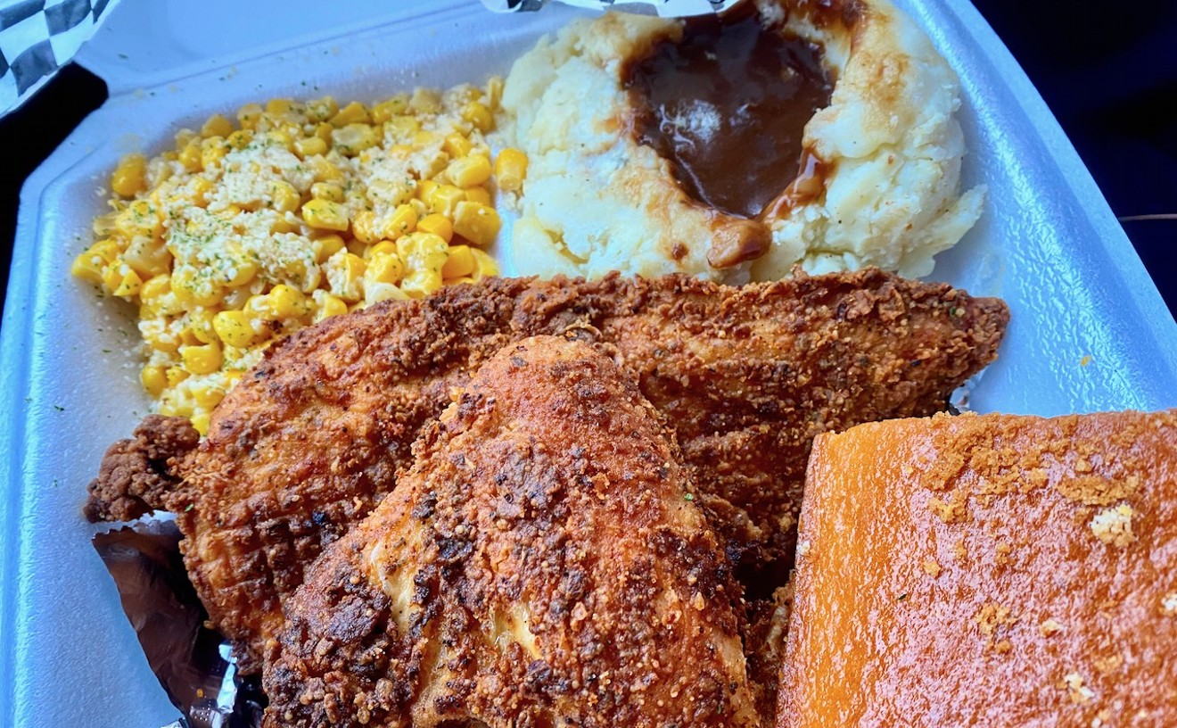 Two-piece chicken entree with corn and mashed potatoes and a square of cornbread.