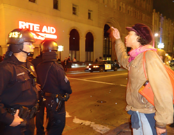 A demonstrator faces off against Oakland police at Sunday's march against Mayor Schaaf's new ban on nighttime street marches. - DARWIN BONDGRAHAM