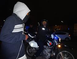 A Motorcycle officer orders a demonstrator onto the sidewalk. - DARWIN BONDGRAHAM