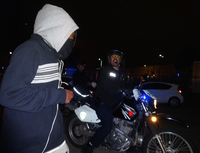 A Motorcycle officer orders a demonstrator onto the sidewalk. - DARWIN BONDGRAHAM