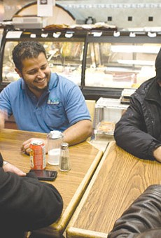 Co-owner Mohsin Sharif and some customers at Oasis Food Market.