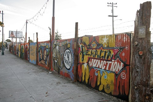 Mural artists have painted the fence surrounding the Peralta Junction site.
